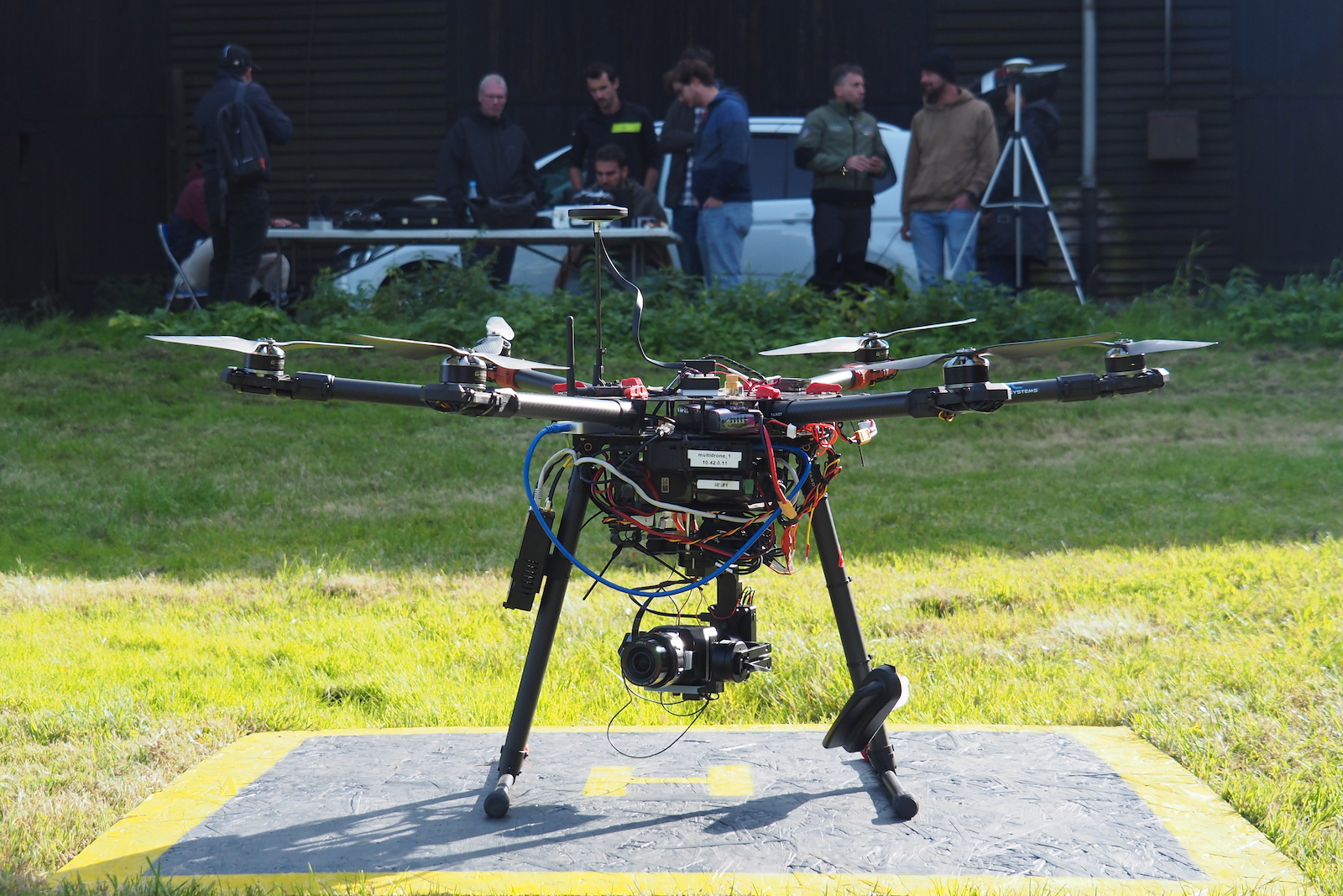 A MultiDrone waits for liftoff, while team-members prepare in the background